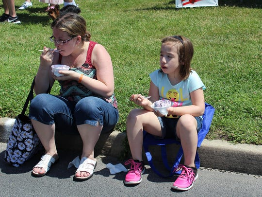 Justina Winkels (left) and her daughter Isabella, 8, take a break from the festival to enjoy some blueberry ice cream.