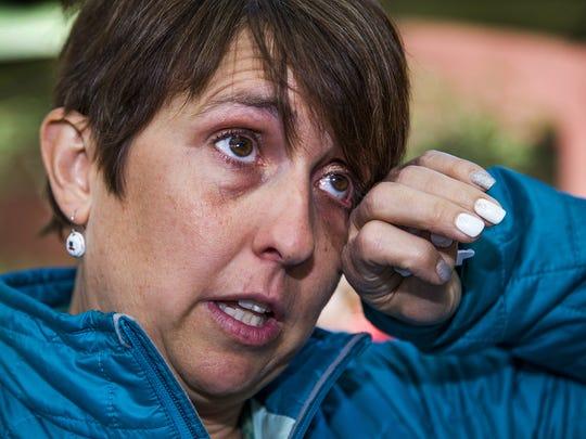 Amanda Marsh wipes away a tear as she talks about her husband.