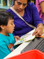Soledad Vasquez  helps her son Jared Vasquez read a