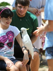 Frances Lebron interacts with Sam Bird, a Cockatoo,