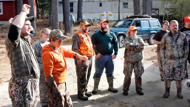 In this photo taken Nov. 12, 2014, successful deer hunters gather at the deer check station in Hillsboro, N.H. Fish and Wildlife officials suspect that interest from local food connoisseurs is helping to level off a drop in the number of hunting license holders nationally, which has been on a steady decline over the last 30 years.