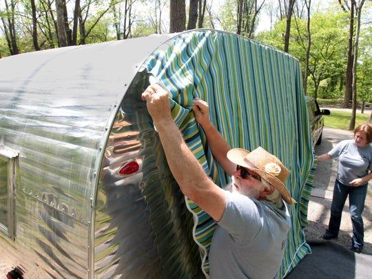 Robert Linck (cq) installs an awning on a 1958, 14-foot-long Fan camping trailer in the campground at Miami Whitwater Forest.  At right is Debbie Immesoete (cq) , owner of Route Fifty (cq) Campers, which rents vintage campers.  Linck is a friend who helps out in setting up the trailers.
