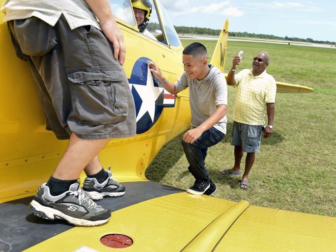 Bryan Cruz, 17, (center right) of Humacao, Puerto Rico steps onto the wing of a North American AT-6 Texan airplane Saturday as his uncle, Francisco Cruz of West Palm Beach (right) takes a video during the 2016 Vero Beach Air Show at the Vero Beach Regional Airport. 'It's pretty cool. I'm excited,' said Bryan Cruz before taking a ride on the AT-6. The air show features aerial performances, static aircraft displays, a family fun zone, local food and drink vendors, and more and continues from 9 a.m. to 4 p.m. on Sunday.