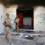 Libyan military guards check one of the U.S. Consulate's burned-out buildings during a visit by Libyan President Mohammed el-Megarif on Sept. 14, 2012.