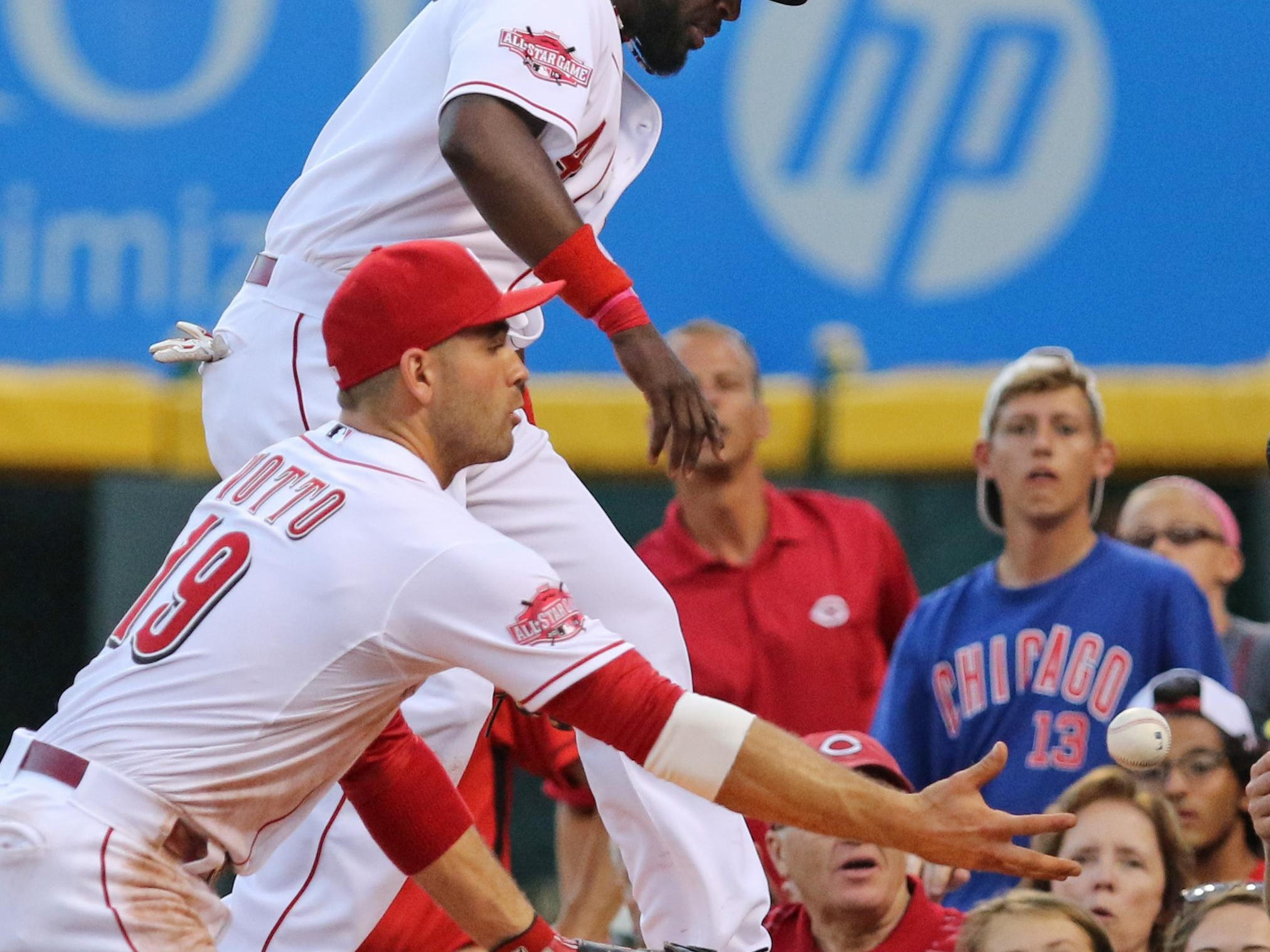 Cincinnati's Brandon Phillips, top, and Joey Votto go to the tarp, but can't come up with a ball hit by Addison Russell.