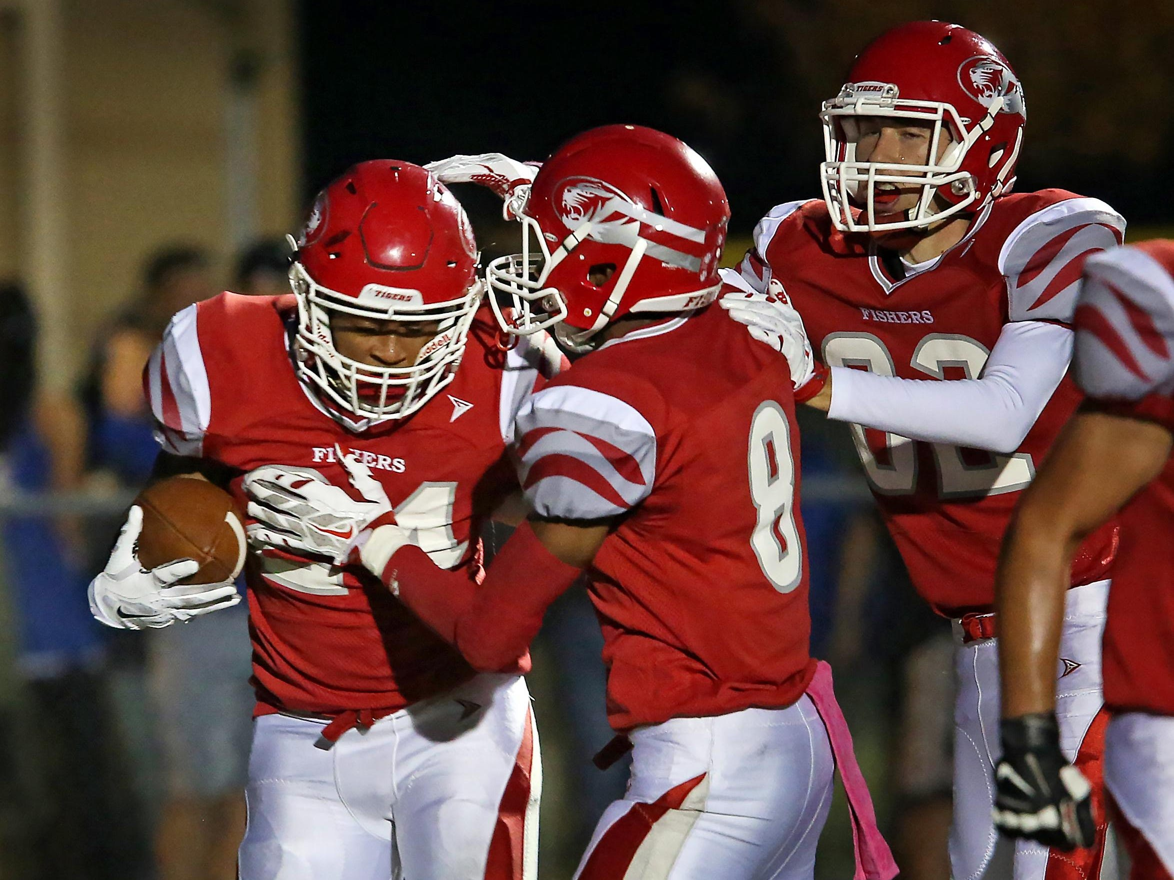 Jermaine Huddleston (left) is congratulated by teammates after he scored Fishers' first TD in the Tigers' win over Hamilton Southeastern.