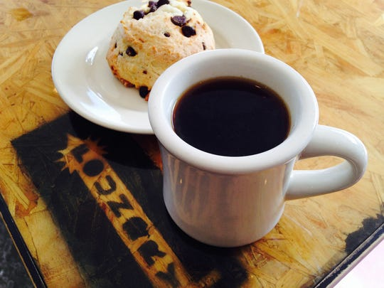 "A ""bottomless"" mug of brewed Julian Coffee Roasters coffee alongside a chocolate chip scone from Circle City Sweets at Foundry Provisions, 236 E 16th St."