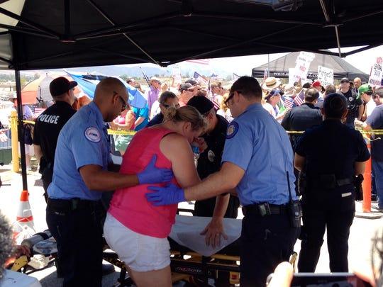 Border Patrol agents treat a woman in Murrieta on Friday, July 4, 2014.