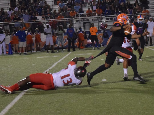 Sul Ross' Zack Roberson (13, left) grabs hold of Louisiana College quarterback D'Ondre Joseph (4, right) as Joseph looks to pass.