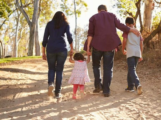 Mixed race family walking on rural path, close up