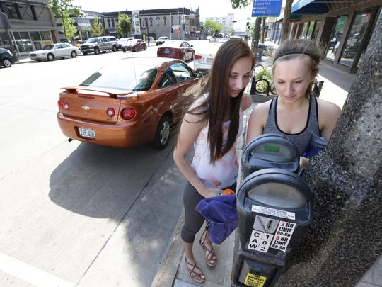 Kaylie Nytes (left) and Emily Paul of Kaukauna feed a parking meter in downtown Appleton before heading to a yoga class.