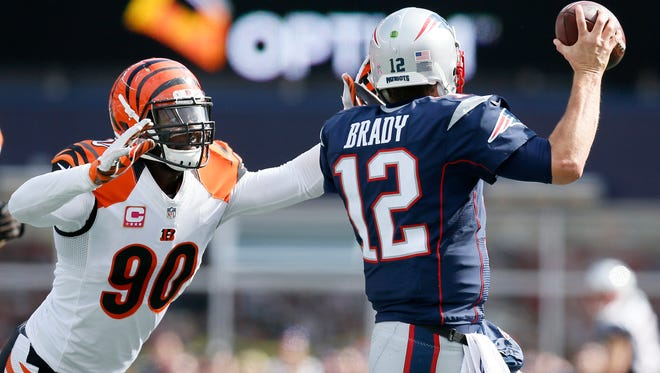 Cincinnati Bengals defensive end Michael Johnson (90) forces New England Patriots quarterback Tom Brady (12) outside of the pocket, leading to an intentional grounding penalty in the first quarter of the NFL Week 6 game between the New England Patriots and the Cincinnati Bengals at Gillette Stadium in Foxboro, Mass., on Sunday, Oct. 16, 2016. At halftime, the Patriots led 10-7.