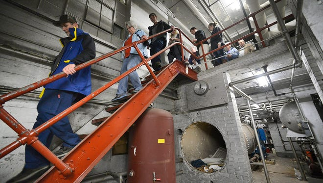 Parents descend a flight of metal stairs into the original 1917 boiler room at St. Cloud Tech during a tour Wednesday that preceded a presentation on the district's $167 million bond referendum.
