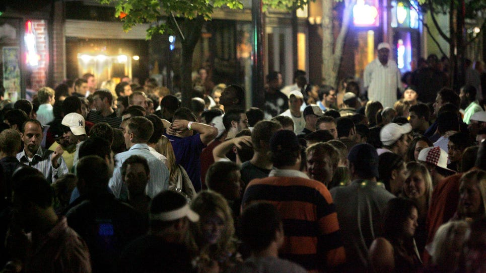 The pedestrian mall is filled with people as bars empty