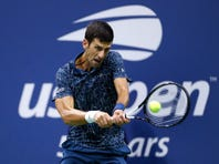 "FILE - In this Sept. 9, 2018, file photo, Novak Djokovic, of Serbia, returns a shot to Juan Martin del Potro, of Argentina, during the men's final of the U.S. Open tennis tournament in New York. Djokovic is fretting about ""harsh"" restrictions on players' entourages and other ""extreme"" changes proposed for the U.S. Open, if it is played starting in August. (AP Photo/Adam Hunger, File)"