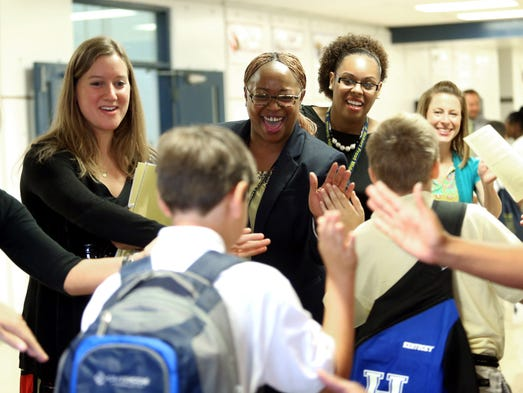 From left, teacher Shelby Daeschner, goal clarity coach LaRhonda Mathies, and interventionist Whitney Hodge high-five students upon their entry to Robert Frost Sixth-Grade Academy on the first day of school. Aug. 13, 2014.