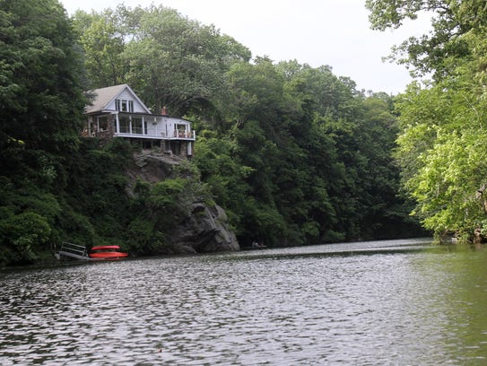 A house sits on a cliff overlooking the Croton River