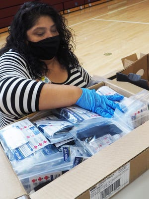 Monica Gamboa was one of the volunteers Wednesday who packed washable face coverings, hand sanitizer and education material into boxes that will be distributed to the community.