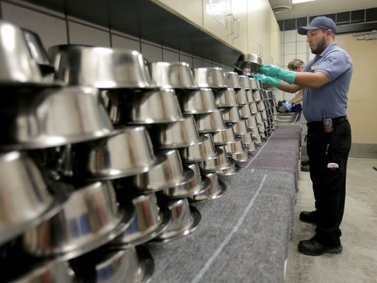 Animal Services employees clean and sanitize pet bowls