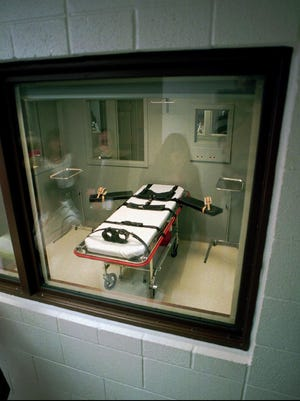 Reflections of people appear in the window while viewing the execution room at Oregon State Penitentiary in Salem, Aug. 7, 1996.