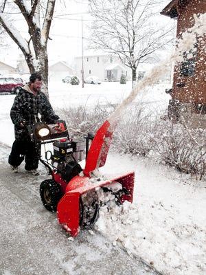Isidro Alvarado uses a snowblower on his driveway in Green Bay.