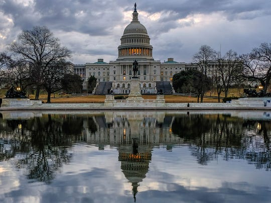 Clouds are reflected in the U.S. Capitol reflecting pool at daybreak in Washington as day three of the government shutdown continued, Jan. 22, 2018.