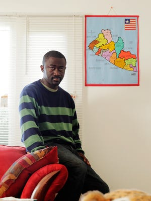 Emmanuel Massaley 40 of Waterford Township holds a map of Liberia at his home in Waterford Township on Friday October 10, 2014. Massaley's grandson died of the Ebola virus and his daughter Delphin Massaley 20, the boy's mother, is ill with the disease now in Montserrado, Liberia an undergoing treatment.