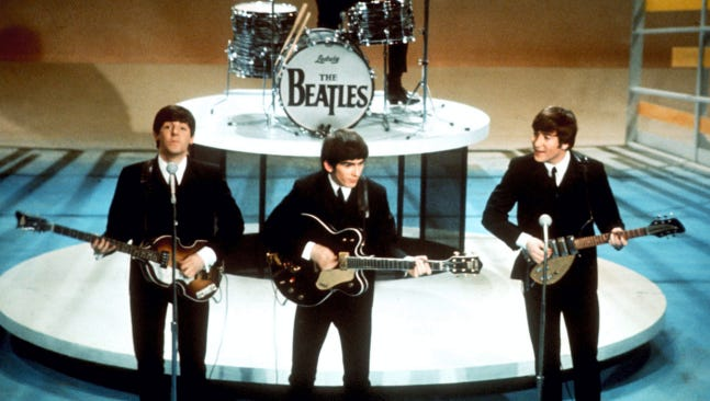 """The Beatles perform on the CBS """"Ed Sullivan Show"""" in New York in this Feb. 9, 1964 photo. Ringo Starr plays drums and playing guitars from left are Paul McCartney, George Harrison and John Lennon. An estimated 73 million Americans tuned in, the largest ever for a TV show at the time, or three times the amount of people who watched the latest 'American Idol' finale, according to the Nielsen Co."""