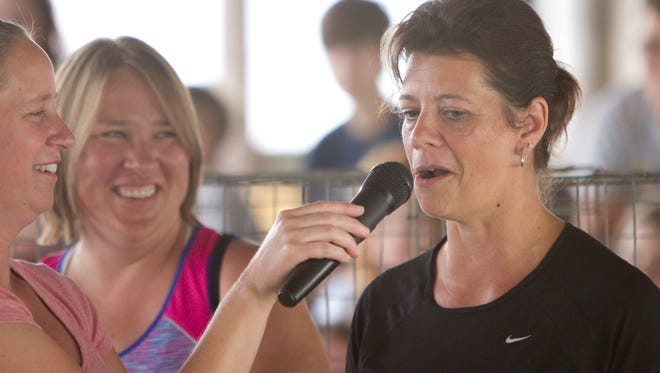 4-H poultry superintendent Sarah Wylie, left, holds the microphone to 4-H educator Roxanne Turner, competing in the 15-and-up age group human rooster crowing contest. Turner's crow earned her first place for her effort.