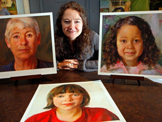 Artist Rose Frantzen poses at her Old City Hall Gallery with three of her paintings Nov. 24, 2009, in Maquoketa, Iowa.