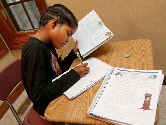 Debjani Dawodu works on a spelling lesson Wednesday, December 17, 2014, in her Lafayette home. Debjani's mother, Carlee Dawodu, also has three other daughters. She prefers homeschooling as a way to keep the children together.