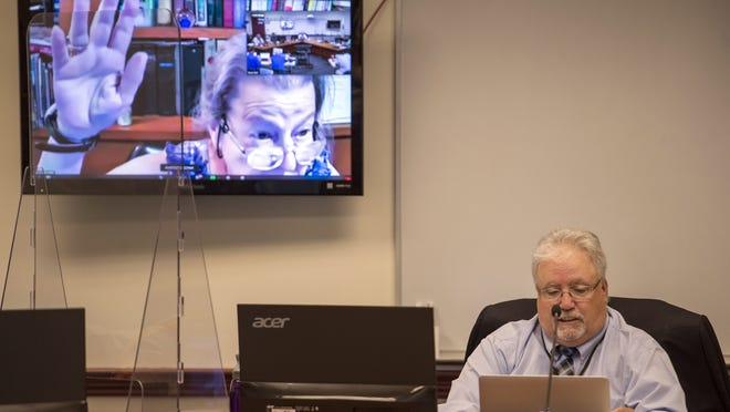 Natick Town Moderator Frank Foss, right, reads the rules for the remote meeting, as Precinct 5 representative Erica Ball raises her hand via Zoom, during Natick's spring annual Town Meeting, held virtually because of the COVID-19 pandemic, July 11, 2020.
