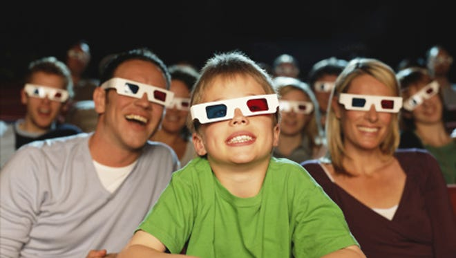 Parents and son (9-11) watching 3-D movie (focus on boy laughing)