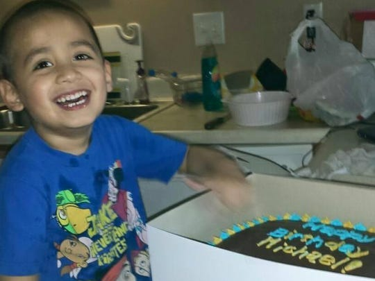 Michael Herzog, 4, poses with his birthday cake from