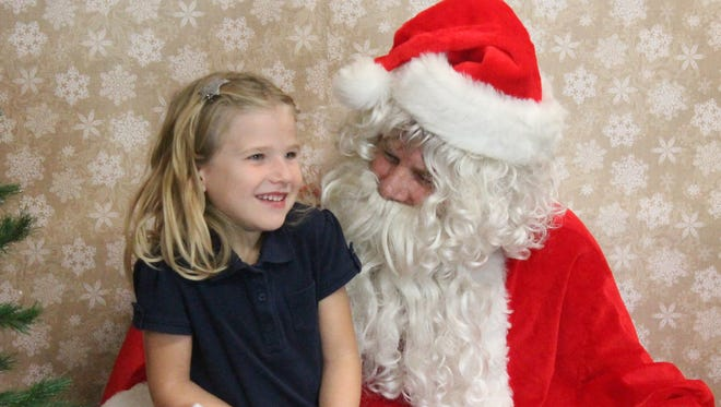 Children lined up at Amy Tillotson-State Farm Insurance Agency, 1018 Vermont Ave., to take photos with the Wizard of the North Pole and tell Santa what they want for Christmas. The event was from 3 p.m. to 7 p.m. Friday.