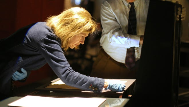 Beth Gerber, preservation manager for the Cincinnati Museum Center, handles one of the few copies of the Declaration of Independence.
