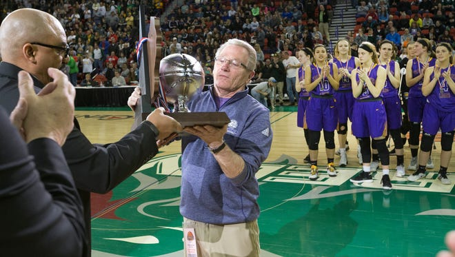 New Berlin Eisenhower head coach Gary Schmidt accepts the WIAA Division 2 runner-up place trophy on Saturday night at the Resch Center in Ashwaubenon.