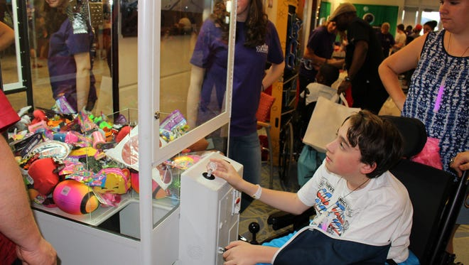 A patient plays a carnival game during The Marisa Tufaro Foundation's boardwalk-themed Family Fun Night at Children's Specialized Hospital in New Brunswick on Tuesday night.