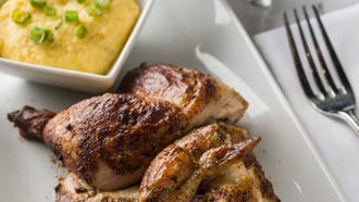 Half chicken roasted on an open flame with Zea's signature seasoning is plated with grilled corn in homemade grits, garnished with thinly sliced green onions.