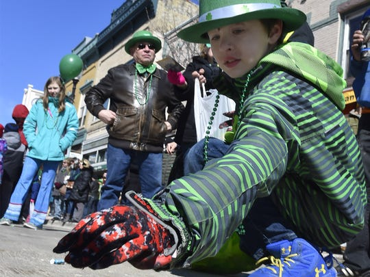 An appropriately dressed Remington Peters of Sturgeon Bay picks up candy tossed from a float along last year's St. Patrick's Day Parade route.