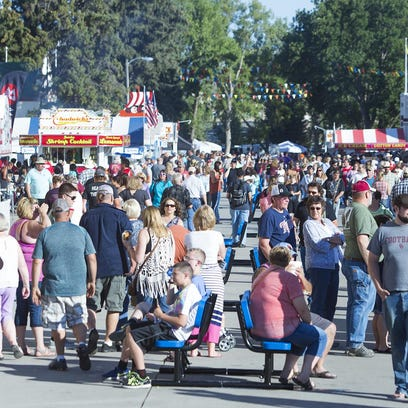 Fair goers walk along food alley during the dinner