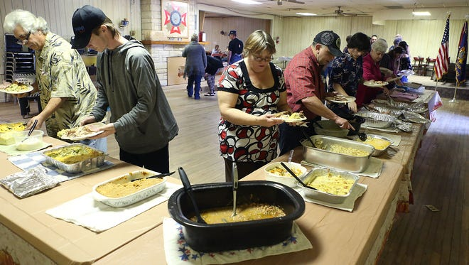 Guests help themselves to a feast at the Veterans of Foreign Affairs Post 1815 who opened its doors for a Thanksgiving Day Thursday, Nov. 23, 2017.