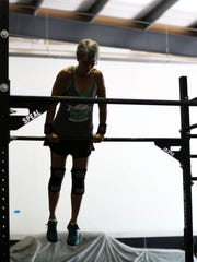 Karin Gogolsky, 62, of Chili does a bar muscle up while
