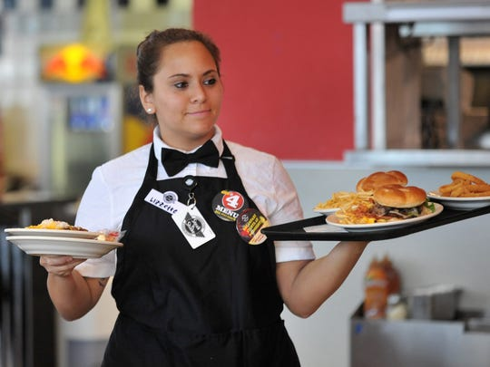 Server Lizzette Menendez is shown delivering meals