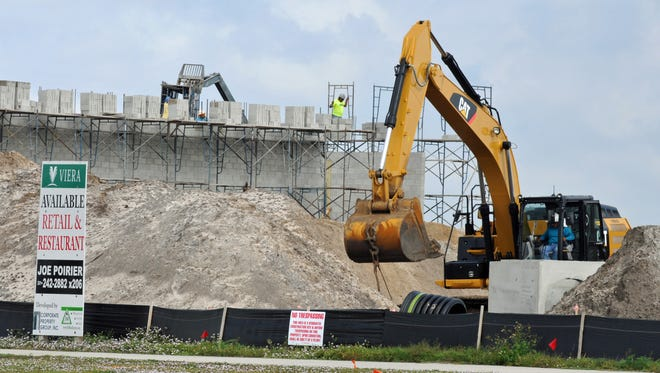 A backhoe operator works along Lake Andrew Drive in Viera on the new 12,000-square-foot PetSmart. If there wasn't a moratorium on transportation impact fees, the fee for this building would have been $70,000.