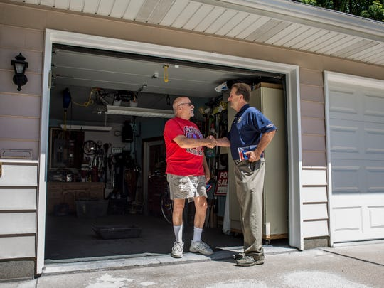 Alan Sanborn, of Richmond Township, right, shakes hands with Mark Gaines in front of his home while walking door-to-door to promote his campaign Tuesday, July 26, 2016 on Sanborn Street in Port Huron. Sanborn, a republican, is running for Congress in Michigan's 10th Congressional District