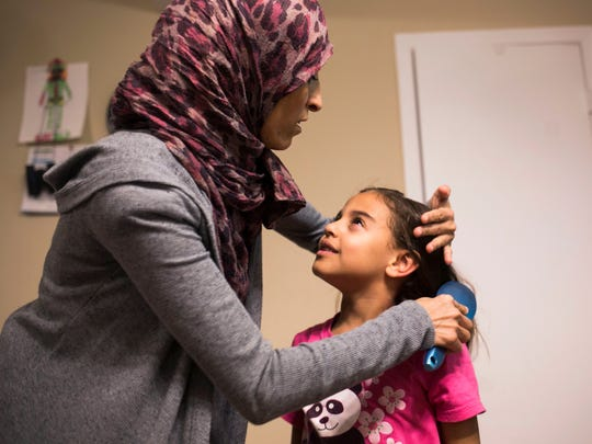 Mariam Shukri, 6, looks up at her mother, Mufida Ammar, while having her hair brushed Thursday, February 2, 2017 in Clemson.