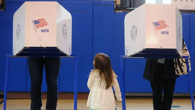 Brigit Mulligan (right) casts her vote as her daughter, Giovanna Candido, watches during a primary election April 19, 2016, at Sanford Street School in Glens Falls, N.Y.