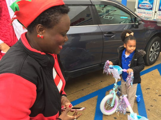 J.S. Clark Elementary Principal Kenya Roberts watches as one of her students, 4-year-old Hailey Mosley, plays with her new bicycle for the first time at Academy Sports and Outdoors on East Bert Kouns Industrial Loop  on Dec. 18.