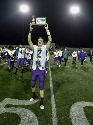 Salinas' Kelly Mcdermott hoists the championship trophy to the crowd as he celebrates defeating Milpitas during a Central Coast Section: Open Division I Championship football game between the Salinas Cowboys and the Milpitas Trojans at Independence High School on Friday, December 1, 2017 in San Jose, Calif. Vernon McKnight/for The Californian